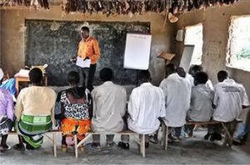 Unterricht in Hütte, vermutlich aus Lehm: 7 Menschen sitzen, vor ihnen steht ein Mann in orangenem Hemd neben einem Flipchart.