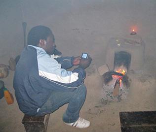Im verrauchten Raum aus Lehm sitzt ein Mann auf einem Holzschemel und hält wohl ein Handy. Vor ihm brennt ein Feuer im Ofen.