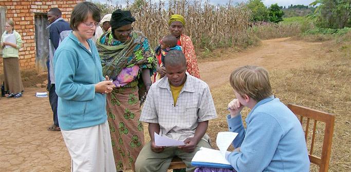 Ländliche Gegend. Neben einer Dame mit Clipboard sitzt ein Mann und stehen mehrere Frauen. Der Mann betrachtet einen Zettel.