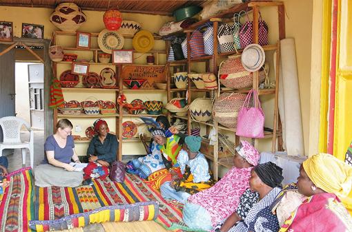 Raum: Regale voller Flechtwaren. Die Wand entlang sitzen auf bunten Teppichen viele afrikanische Damen sowie eine europäische.