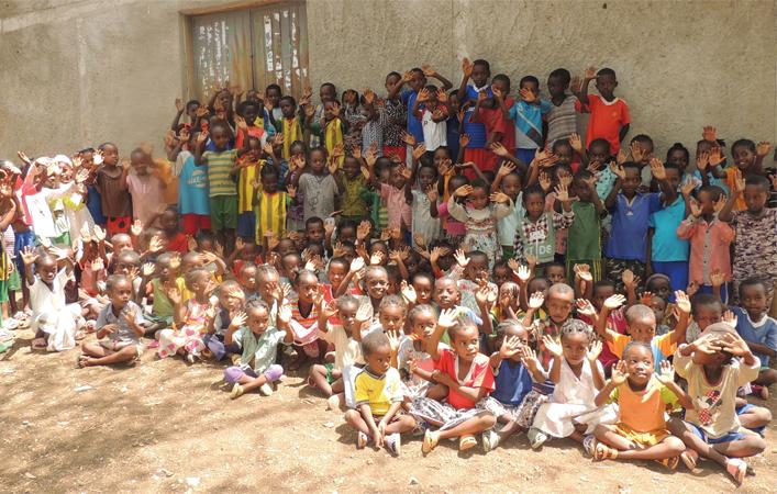 Vor einer Lehmwand stehen viele dunkelhäutige Kinder in bunten Hemden und Hosen eng zusammen. Vor ihnen sitzen viele weitere.