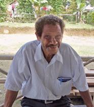 Mann mit Schnurrbart und krausem, grauschwarzen Haar lächelt in die Kamera. In der Tasche seines Hemdes steckt ein Notizbuch.