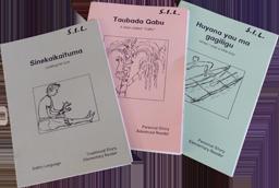 Drei Geschichtenhefte mit Text und Strichzeichnungen darauf. Das linke ist hellgrau, das mittlere rosa, das rechte hellblau.