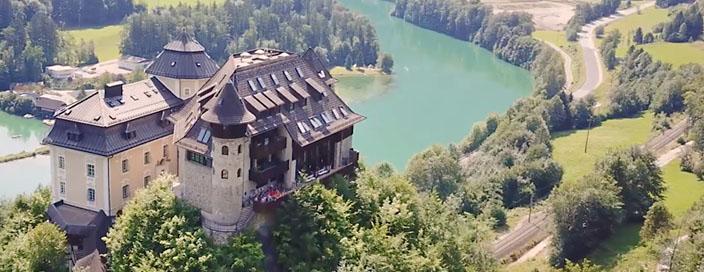 Ein braun-weiß-gelbes Schloss mit braun-grauen Burgteil. Dahinter ein türkiser Fluss, von Bäumen gesäumt, daneben Zuggleise.