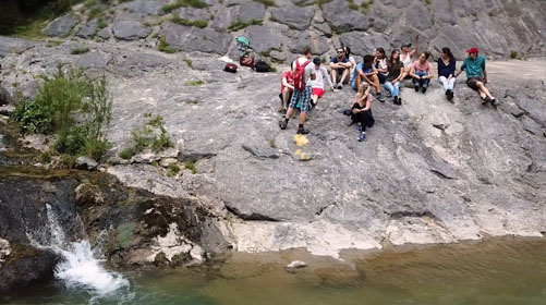 Auf der Felsböschung vor einem Fluss sitzt eine Gruppe von Menschen beisammen. Ein Mann steht, den Rucksack am Rücken.