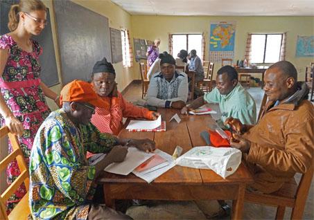 Fünf afrikanische Männer arbeiten an einem Holztisch, vor ihnen liegen Zettel. Eine Dame steht daneben und sieht zu ihnen.