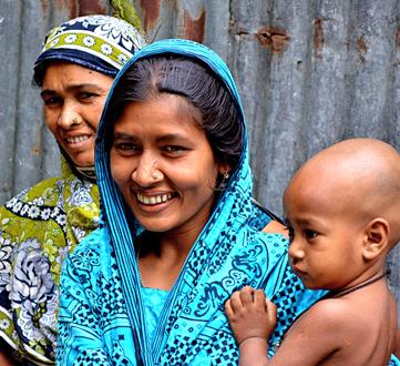 Zwei Frauen mit Kopftuch in Bangladesh, die vordere hält ein Baby und trägt ein leuchtend hellblaues, gemustertes Tuch.