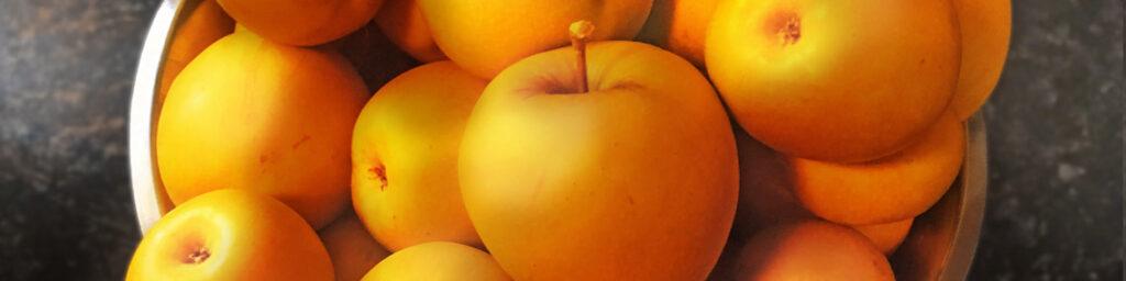 Goldene Äpfel in einer silbernen Schüssel, darunter eine dunkelgrau gemusterte Platte