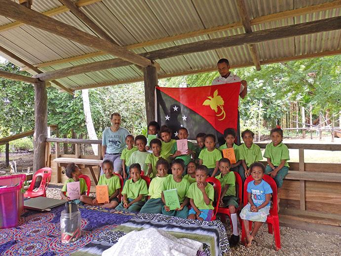 Unter einem Wellblechdach sitzen Kinder, einige halten bunte Hefte. Hinter ihnen hält ein Mann die Flagge Papua-Neuguineas.