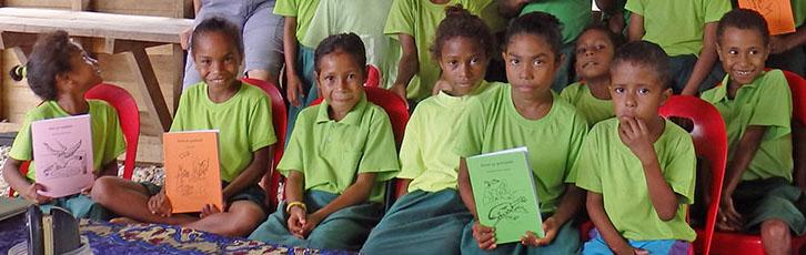 Einige der Kinder: schwarze Haare, mittelbrauner Hautton, leuchtend-hellgrüne T-Shirts. Drei halten Geschichtenhefte hoch.