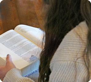 Foto: Frau mit langem, dunkelbraunen Haar von hinten gesehen, sitzt mit offener Bibel auf dem Schoß. Vor ihr ein Parkettboden.