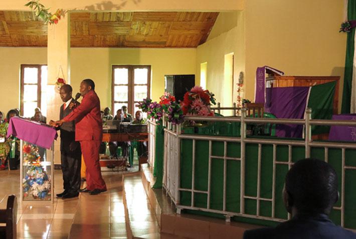 Hinterer Saalbereich. Zwei dunkelhäutige Männer im Anzug (rot o. schwarz) hinter einem Rednerpult, das vor einem Podium steht.
