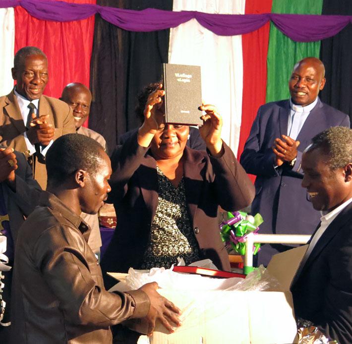 Eine afrikanische Dame hält ein Buch hoch. Afrikanische Männer hinter ihr applaudieren, zwei vor ihr halten eine offene Kiste.