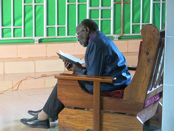 Ein dunkelhäutiger Mann mit Brille sitzt auf einem großen Holzsessel und liest in einem schwarzen Buch.