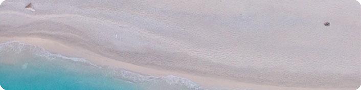 Trockener Sandstrand von oben, unten beginnt das Meer.