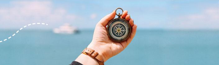Im Hintergrund das Meer, darauf ein Schiff, von dem eine gestrichelte Linie wegführt. Im Vordergrund eine Hand mit Kompass.