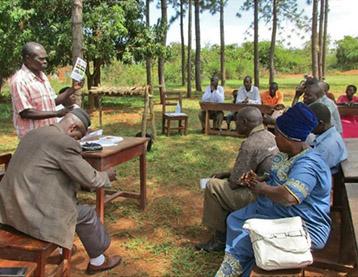 Wiese, dahinter Bäume und Büsche. Auf Bänken sitzen afrikanische Menschen, einer, der Sprecher, steht davor vor einem Tisch.