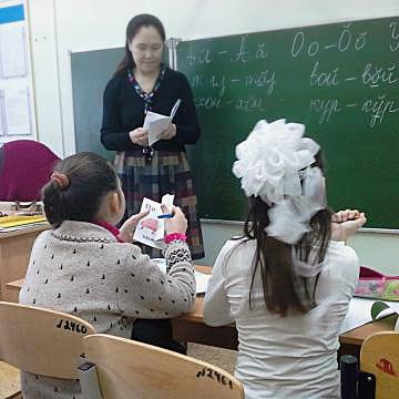 Eine Lehrerin steht vor einer beschriebenen Tafel, vor ihr sitzen zwei Schulmädchen mit heller Kleidung und dunklen Haaren.