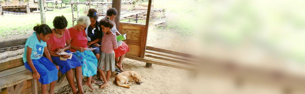 Unterstand: Mädchen und Frauen aus Ozeanien sitzen auf Holzbank und lesen Papiere bzw. ein Büchlein. Davor schläft ein Hund.