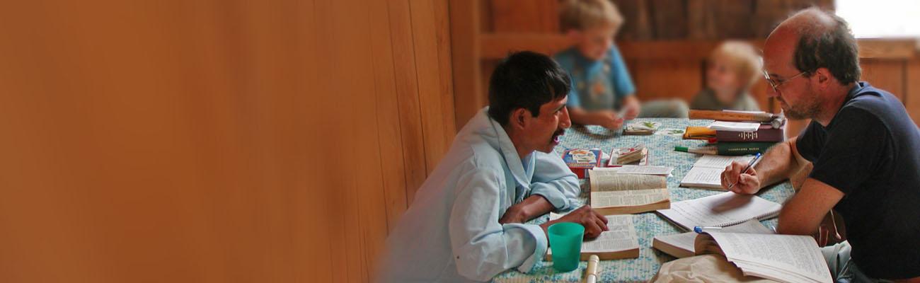 Holzhaus: 2 Männer, einer mexikanisch, einer mit heller Haut, sitzen an Tisch. Zwischen ihnen Bücher. Im Hintergund 2 Buben.