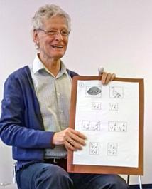 Ein lachender Mann mit weißen Haaren, Brille und blauem Pullover hält eine Tafel mit Zeichnungen und seltsamen Buchstaben.
