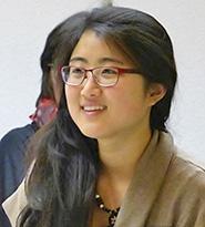 Das Gesicht einer lächelnden, asiatisch aussehenden Dame mit langem, schwarzen Haar, roter Brille, Kette und beigem Sweater.