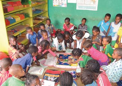 Kinder von dunkler Hautfarbe sitzen im Kreis versammelt über einem Afrikakarten-Lernpuzzle. Links ein Kasten mit Materialien.