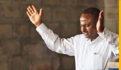 Mann mit dunkler Haut- und Haarfarbe in weißem Hemd vor einer Steinmauer. Er betet, die Hände gehoben, die Augen geschlossen.