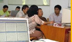 Besprechung: Asiatische Menschen, rechts ein Computer, im Vordergrund ein Laptop, er zeigt einige Textfelder nebeneinander.