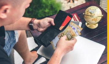 Mann holt über dunklem Holztisch, auf dem ein kleiner Globus steht und ein Laptop liegt, Euroscheine aus seiner Geldbörse.