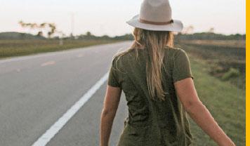 Von hinten gesehen: eine Frau, grünes Hemd, lange blonde Haare, weißer Hut, geht den Rand einer Landstraße entlang.