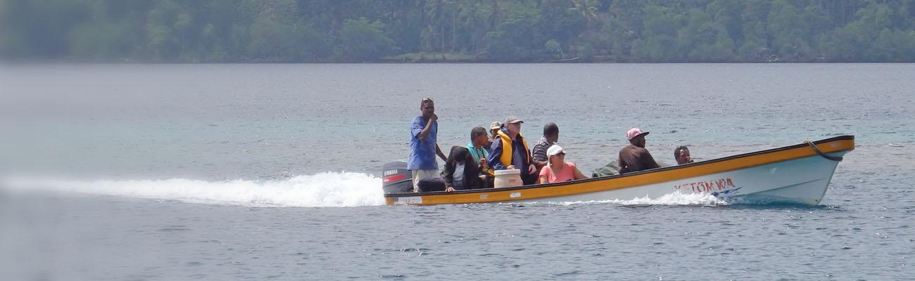 Motorboot fährt durch blaugraue See. Die Insassen sind meist von dunkler Hautfarbe, zwei von heller. Dahinter: Büsche/Bäume.