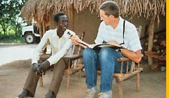 Hütte mit Strohdach, dahinter ein Auto. Davor sitzt ein afrikanischer Mann. Ein hellhäutiger Mann hält ihm ein Mikrofon hin.