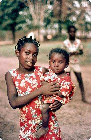 Bäume, Erdboden. Davor ein Bub sowie ein Mädchen in rotem Kleid, das ein im selben Stoff gekleidetes Baby am Arm hält.
