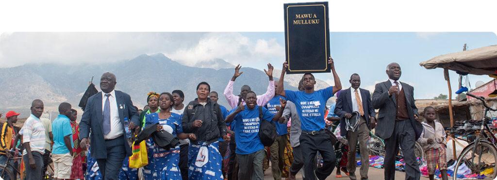 Afrikaner/innen, blau und schwarz gekleidet, gehen auf Straße nebeneinander. Ein Mann hält etwas wie in großes Buch hoch.