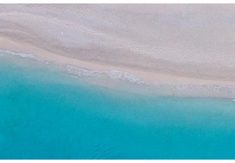 Trockener, hellbeiger Sandstrand von oben gesehen, darunter beginnt das strahlend hellblaue Meer.