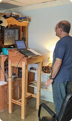 Vor einem Bücherschrank steht ein Mann in blauem Hemd vorm Laptop. Am externen Bildschirm dahinter läuft ein Zoom-Gespräch.