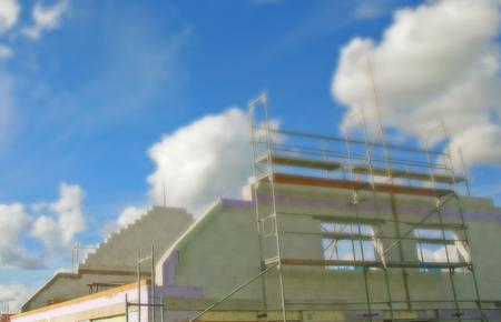 Blauer Himmel mit Wolken, davor oberer Teil eines Gebäudes, das gerade errichtet wird, mit Gerüst davor. Helle Ziegelmauern.