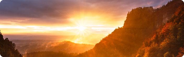 Foto: Unter graublauen Wolken strahlt die Sonne hell in Gelb und Orange über eine baumbewachsene Berglandschaft.