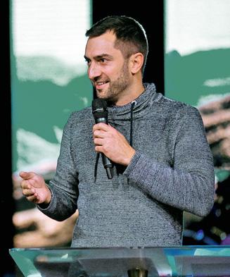 Mann mit schwarzen Haaren und graumeliertem Pullover, mit Mikrofon in der Hand, steht hinter Rednerpult und sieht nach links.