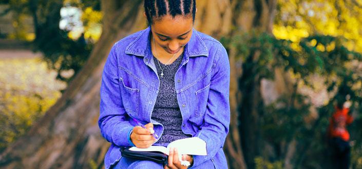 Frau auf Bank vor dickem Baumstamm, trägt lila Jeans und Jeansjacke, hält offenes Buch am Schoß und einen Stift in der Hand.