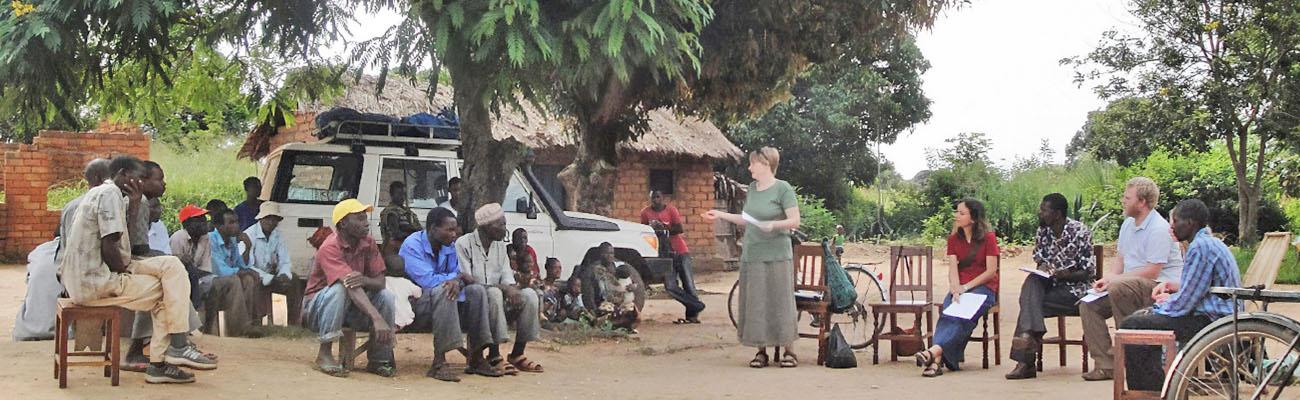 Bäume, ein Auto, ein Ziegelhaus mit Strohdach, dazwischen Menschen unterschiedlicher Hautfarbe auf Sesseln. Eine Frau steht.