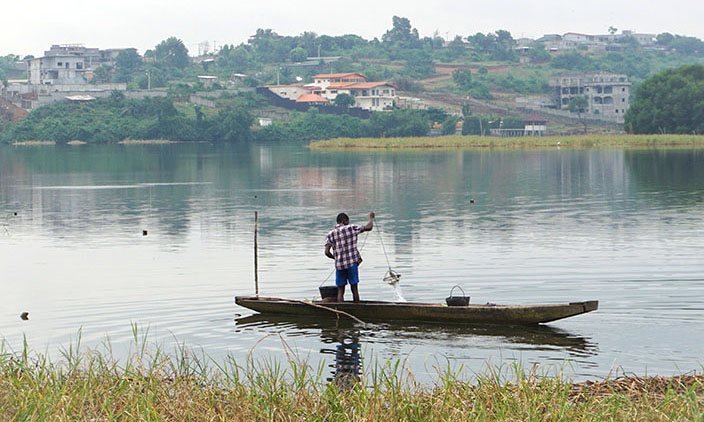 Gewässer mit Kanu, davor Wiese, dahinter ein Hang mit Häusern. Am Kanu hebt ein Mann im karierten Hemd eine kleine Fischreuse.