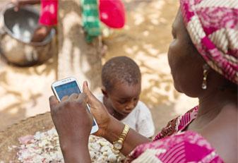 Frau mit rosa-weiß-gemustertem Kleid und Kopftuch tippt auf Handy. Auf ihrem Schoß eine Schüssel, daneben steht ein Kind.