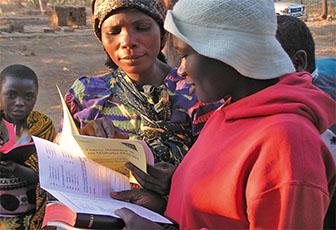 Zwei afrikanische Frauen lesen Hefte aus weißem, blassgelbem und rosanem Papier. Ein Kind schaut in die Kamera. Sandboden.