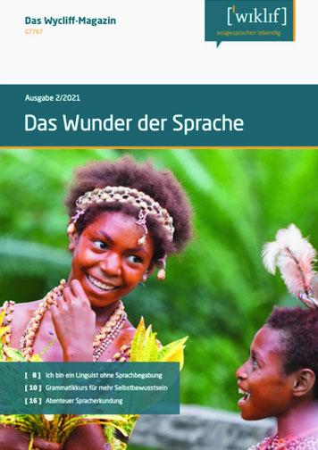 Cover. Text: Das Wunder der Sprache. 2 junge Menschen lachen, dekorative Kleidung, Gesichter rot bemalt, krause, dunkle Haare.